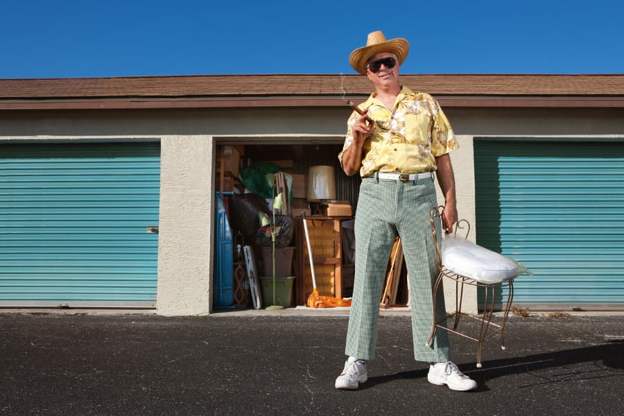 an older man standing in front of storage units