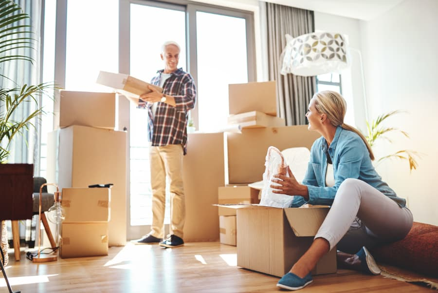 mature couple with several moving boxes in a living room