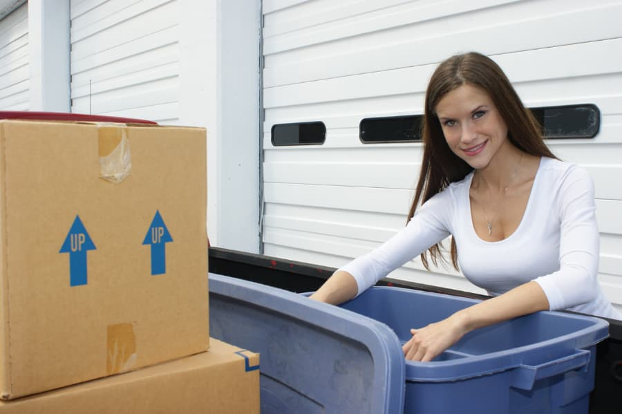 woman in front of storage unit getting ready to lift container out of a truck